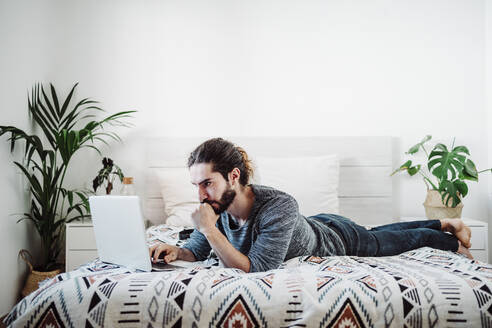 Young man working on laptop while lying on bed at home - EBBF01835