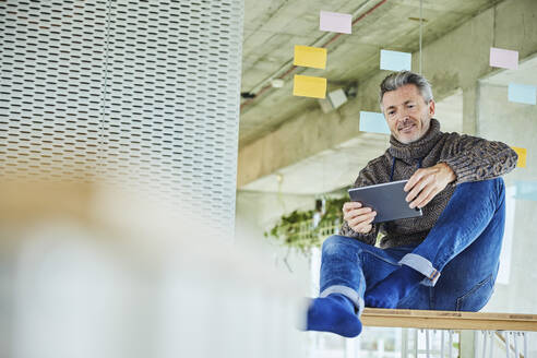Businessman using digital tablet while sitting against glass wall at home - FMKF06883