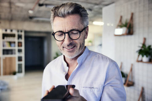 Businessman smiling while talking on mobile phone - FMKF06955