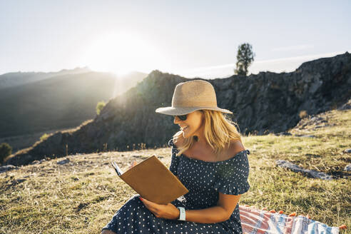 Happy woman reading book while sitting on picnic blanket against mountains on sunny day - MPPF01332