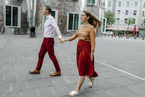 Heterosexual couple holding hands while walking on street in city - OGF00687