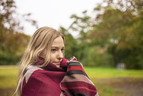 Young woman wrapped in scarf at park during autumn - BFRF02331