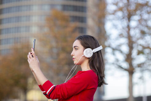Woman with headphones taking selfie on mobile phone - JCCMF00250