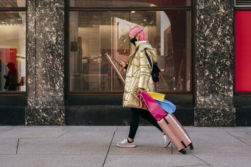 Young woman wearing face mask using mobile phone while walking with shopping bags and luggage on footpath - MARF00036
