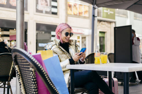 Woman smiling while using mobile phone sitting at sidewalk cafe - MARF00039