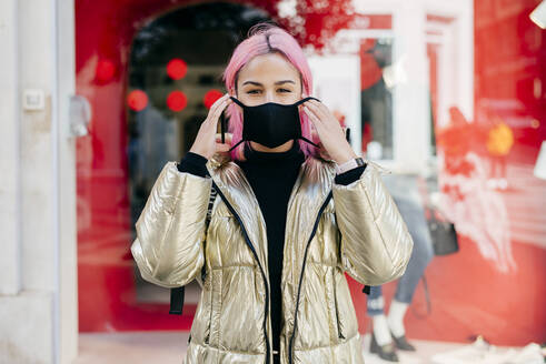Pink hair woman wearing face mask while standing outdoors - MARF00042