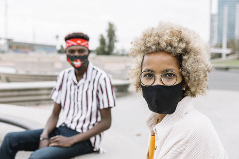Man and woman wearing face mask staring while sitting on bench - XLGF00908