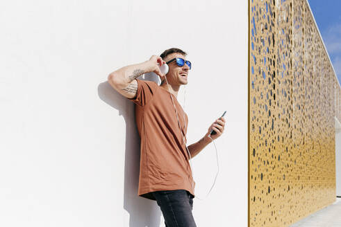 Happy man with mobile phone listening music through headphones while leaning on wall - MARF00050