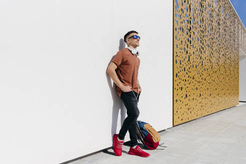 Man wearing sunglasses standing with hand on hip against wall - MARF00053