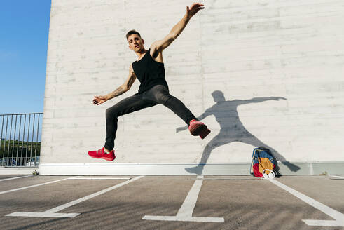 Young man with arms outstretched jumping on footpath during sunny day - MARF00062