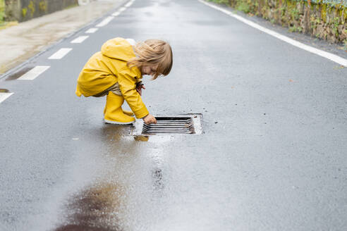 Side view of curious little child in vivid yellow raincoat and rubber boots standing on wet asphalt road after rain - ADSF19287