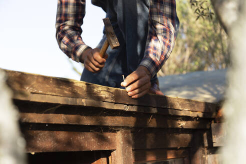 Young man hammering nail on wood during sunny day - JPTF00617