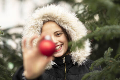 Smiling young woman wearing fur jacket holding Christmas decoration near tree - SGF02722