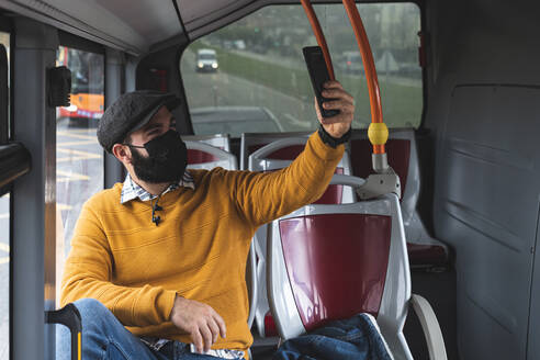 Businessman taking selfie with mask on face while commuting in bus - JAQF00039
