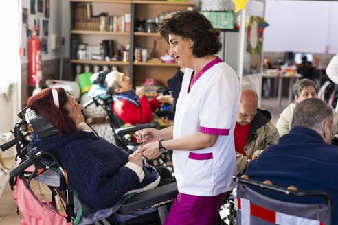 Female caregiver applying nail polish to disabled woman at rehabilitation center - LJF01938