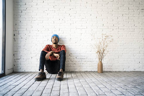 Man wearing knit hat day dreaming while sitting by dried plat vase against white brick wall - RCPF00526