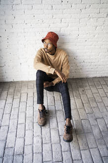 Mid adult man wearing bucket hat day dreaming against white brick wall - RCPF00544