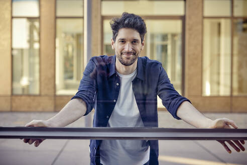Smiling businessman staring while leaning on glass wall - RHF02563