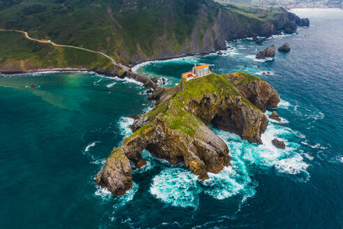 Drone view of paving stone way leading along stone bridge and ridge of rocky hill to lonely house on island Gaztelugatxe surrounded by tranquil sea water under cloudy sky in Basque Country - ADSF19381