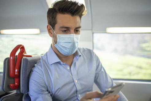 Businessman wearing face mask using smart phone while sitting in train - IFRF00213