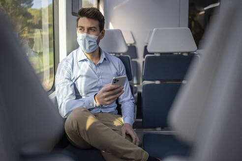 Businessman wearing face mask looking away while using mobile phone sitting in train - IFRF00216