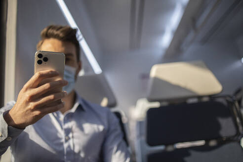Businessman wearing face mask using mobile phone while sitting in train - IFRF00219