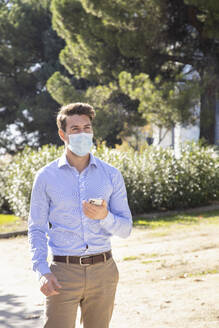 Businessman wearing protective face mask using mobile phone while standing on footpath - IFRF00222
