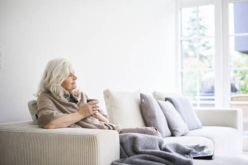 Thoughtful woman with long white hair holding coffee cup while sitting on sofa at apartment - JAHF00033