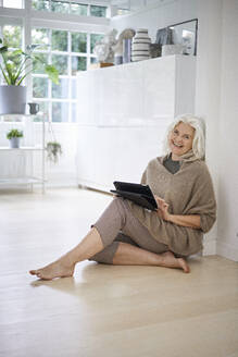 Smiling retired woman sitting on floor with digital tablet in living room at apartment - JAHF00039