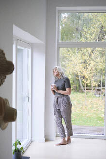 Thoughtful senior woman holding cup while looking through window while leaning on wall at home - JAHF00048