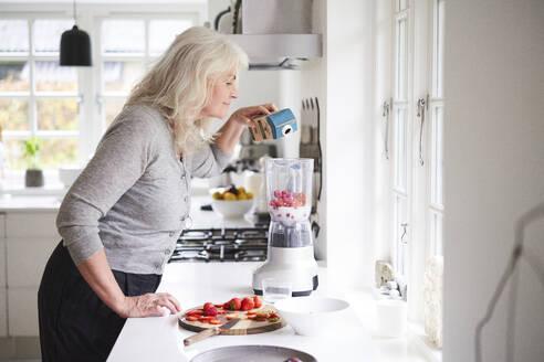 Senior woman pouring milk in processor while preparing strawberry smoothie at kitchen - JAHF00060