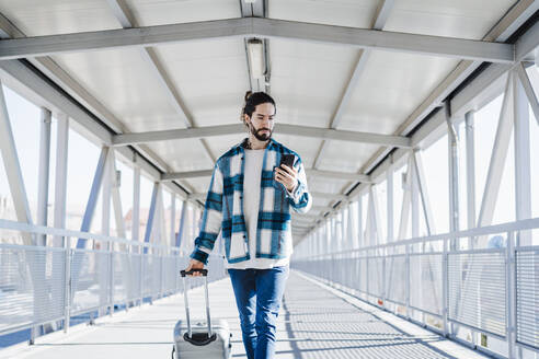 Man using mobile phone while walking with luggage on bridge - EBBF01908