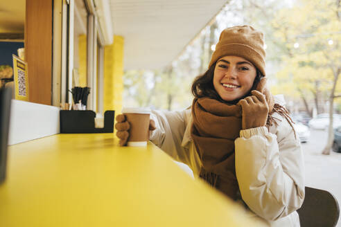 Happy young woman with disposable coffee cup at street cafe during autumn - OYF00298