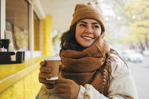 Smiling young woman looking away with disposable coffee cup at street cafe during winter - OYF00301