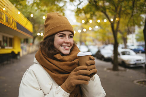Happy woman wearing knit hat day dreaming with disposable coffee cup on street during winter - OYF00307