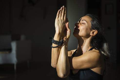 Yogini with eyes closed doing twisted arms meditation in living room in sunlight - MCVF00676