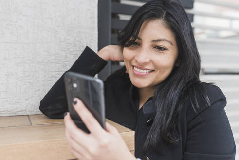 Beautiful woman taking selfie on mobile phone while leaning on wall - DSIF00255