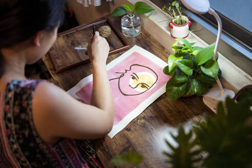 High angle side view of unrecognizable Asian female artist sitting at wooden table and creating picture on paper with paint and brush - ADSF19460