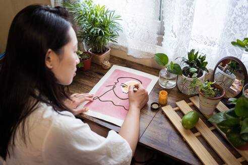 High angle side view of Asian female artist sitting at wooden table and creating picture on paper with paint and brush - ADSF19463