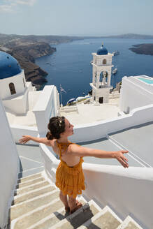 From above of delighted female tourist standing with outstretched arms on stairs of white building and enjoying cityscape of Santorini during summer holiday - ADSF19484