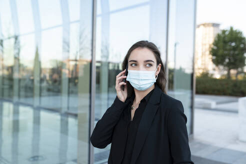 Young businesswoman wearing protective face mask talking on mobile phone while standing against building - JCCMF00285
