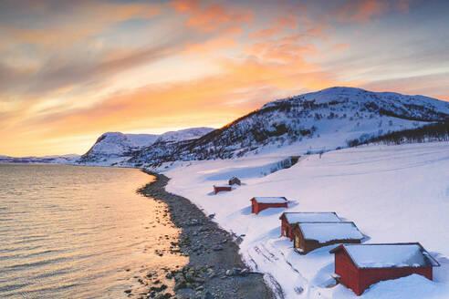 Sunset over red cabins in the snow along Porsangerfjord with North Cape (Nordkapp) on background, Troms og Finnmark, Arctic, Norway, Scandinavia, Europe - RHPLF18961