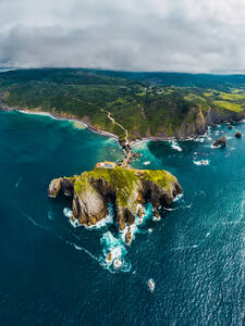 Drone view of paving stone way leading along stone bridge and ridge of rocky hill to lonely house on island Gaztelugatxe surrounded by tranquil sea water under cloudy sky in Basque Country - ADSF19558