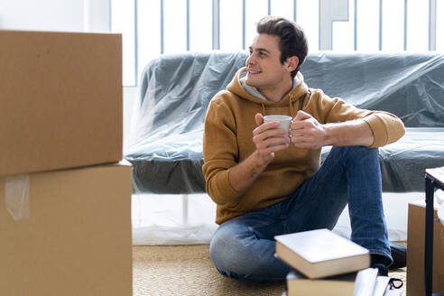 Smiling man with coffee cup looking away while unpacking in new home - GIOF10270
