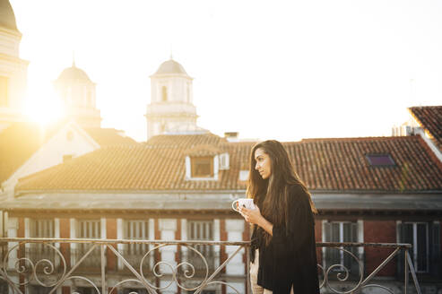 Young woman with coffee cup day dreaming while standing on rooftop in city - JCMF01745