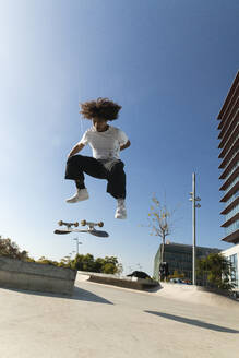 Young sportsman practicing kickflip with skateboard on sunny day - PNAF00379