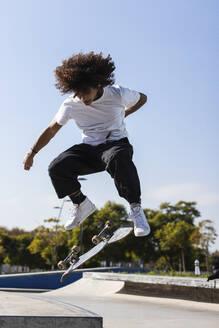 Sportsman skateboarding at skateboard park during sunny day - PNAF00391