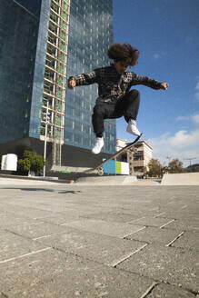 Curly hair sportsman practicing kickflip with skateboard at skateboard park - PNAF00403