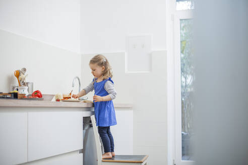 Girl eating food while standing on chair in kitchen at home - KVF00140