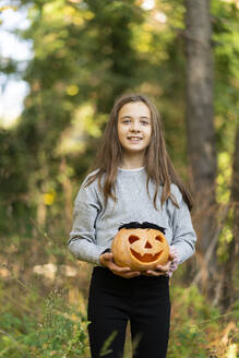 Smiling girl holding Halloween pumpkin while standing at park - XCF00304
